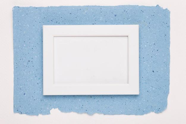 Marco vacío blanco sobre papel azul sobre fondo blanco Foto gratis