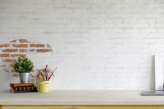 Marco vacío del cartel de la maqueta, suministros de oficina y espacio de copia en la tabla de espacio de trabajo Foto Premium