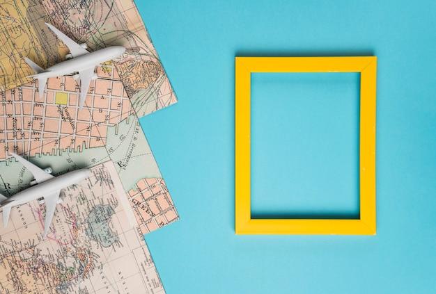 Marco vacío, mapas y avión de juguete. Foto gratis