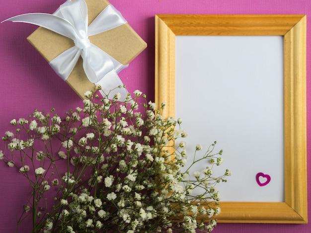 Marco vacío mock up. flores blancas. caja de regalo envuelta. Foto Premium