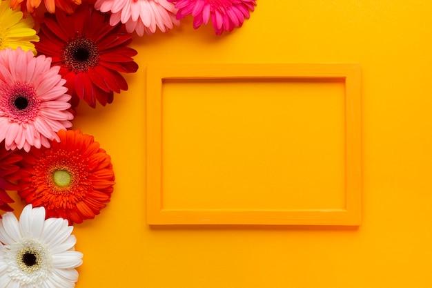 Marco vacío naranja con flores de gerbera Foto gratis