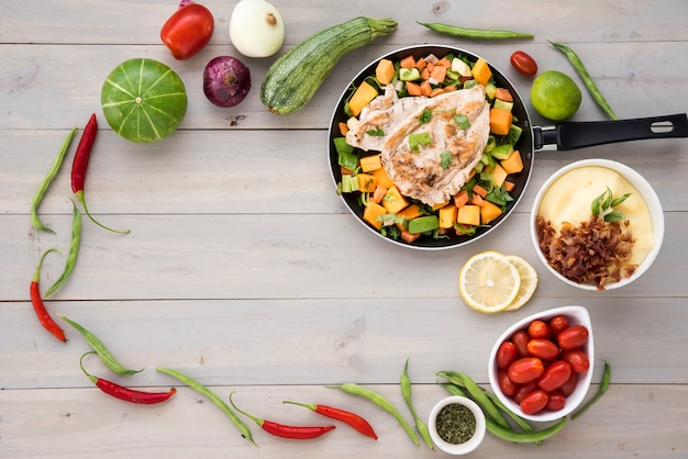Marco de verduras saludables y sartén frita con carne. Foto gratis