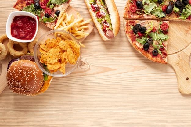 Marco de vista superior con comida rápida y espacio de copia Foto gratis
