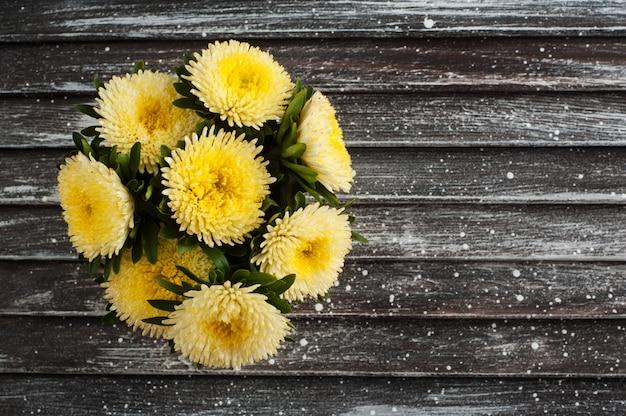 Margaritas amarillas sobre fondo de madera Foto Premium
