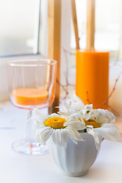 Margaritas blancas se paran en el alféizar de la ventana junto a las velas Foto Premium