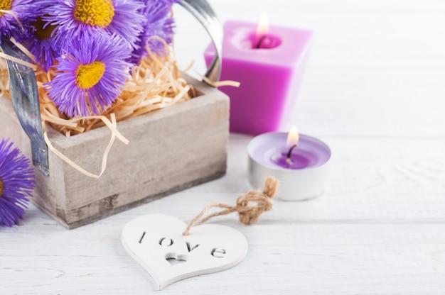 Margaritas púrpuras y velas encendidas en la mesa blanca Foto Premium