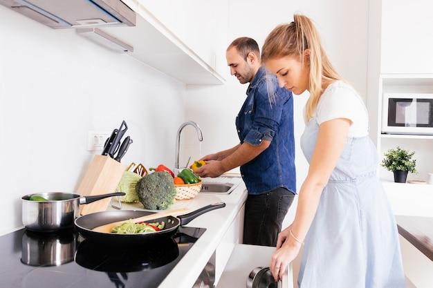 Marido ayudando a su joven esposa rubia preparando la comida en la cocina Foto gratis