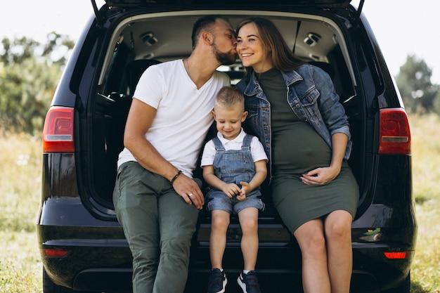 Marido con esposa embarazada y su hijo sentado en carro Foto gratis
