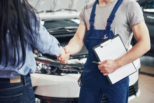Marido mecánico de automóviles y clienta hacen un acuerdo sobre la reparación del automóvil Foto gratis