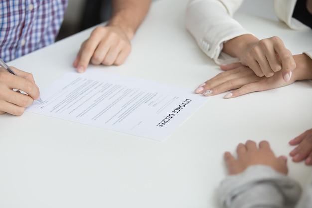 Marido que firma el decreto de divorcio que da permiso para la disolución del matrimonio, primer plano Foto gratis