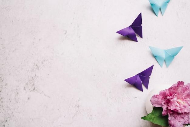 Mariposa de papel origami azul y púrpura con florero Foto gratis