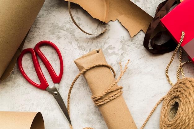 Marrón envuelto caja de regalo con cadena y tijera sobre fondo blanco con textura Foto gratis