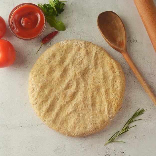 Masa cruda para pizza con salsa de tomate. copia espacio Foto Premium