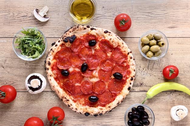Masa de pizza plana con pepperoni Foto gratis