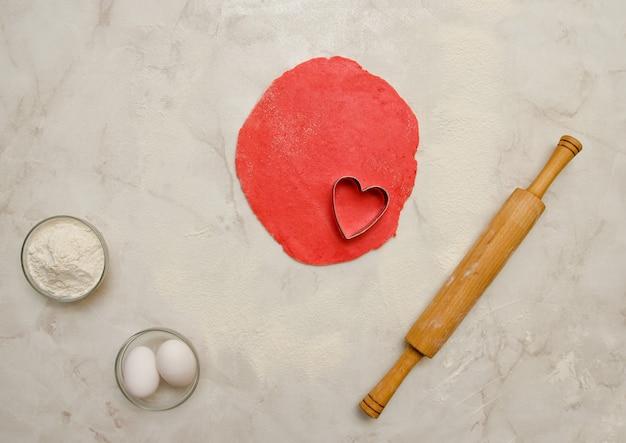 Masa roja con un corazón cortado, rodillo, huevos y harina sobre una mesa blanca. vista superior, espacio para texto Foto Premium