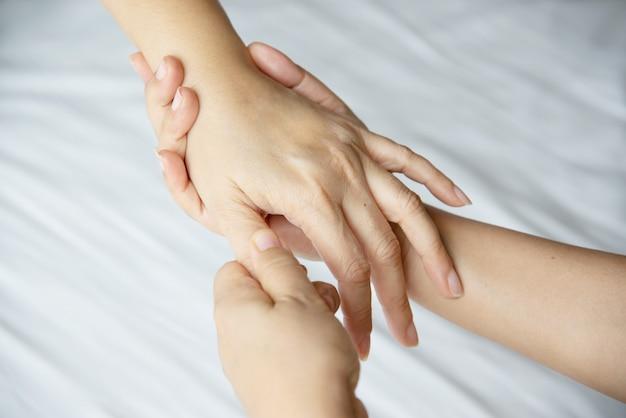 Masaje de manos sobre cama blanca limpia Foto gratis