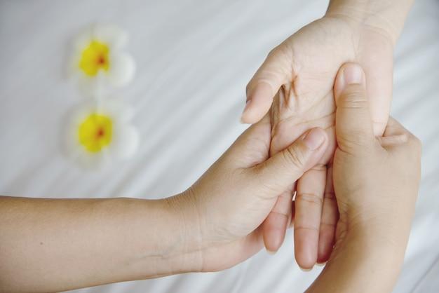 Masaje de spa de manos sobre cama blanca limpia: las personas se relajan con el servicio de masaje de manos Foto gratis