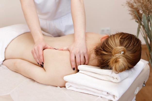 El masajista masajea la espalda de la niña. salón de spa Foto Premium