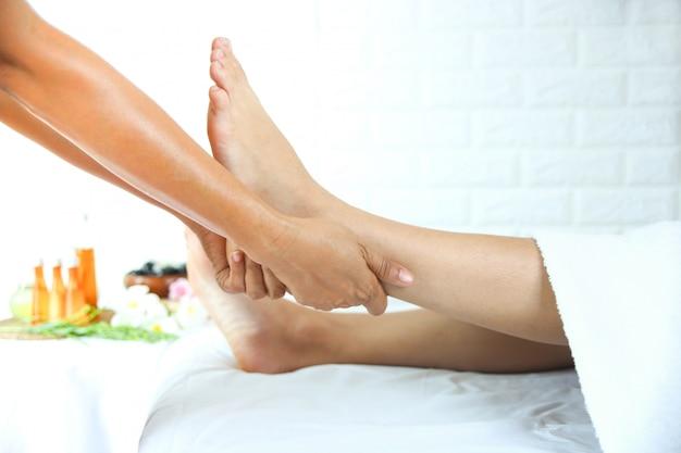 Masajista utiliza dos manos para masaje de pies con mujer joven Foto gratis
