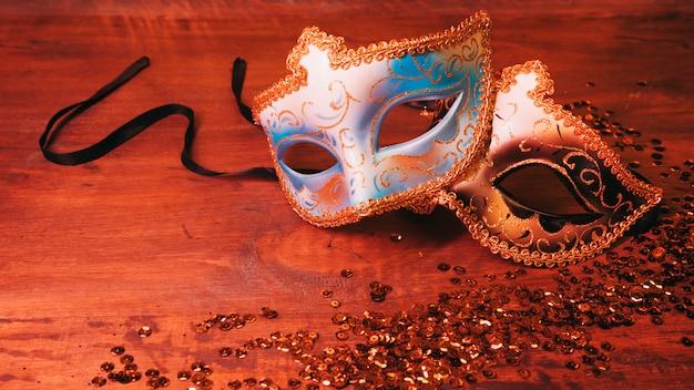 Máscara de carnaval azul y dorada dos con lentejuelas brillantes en el escritorio de madera Foto gratis