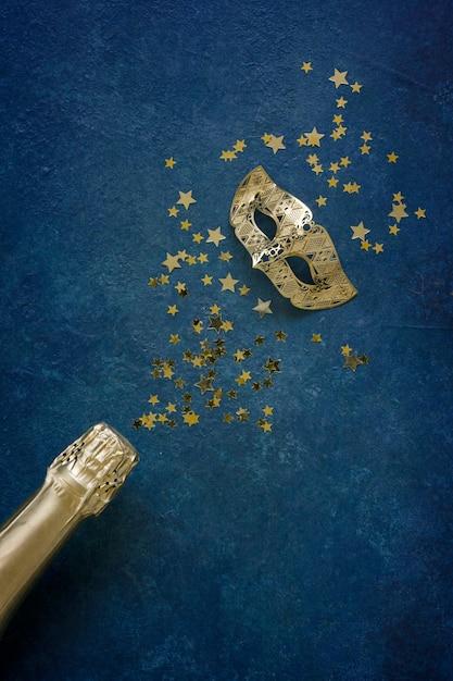 Máscara de carnaval, botella de champán y confeti de brillo dorado. Foto Premium