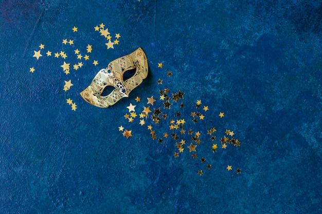 Máscara de carnaval y confeti dorado brillo Foto Premium