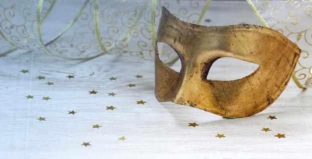 Máscara de carnaval dorado, cinta y estrellas doradas sobre un fondo claro. Foto Premium