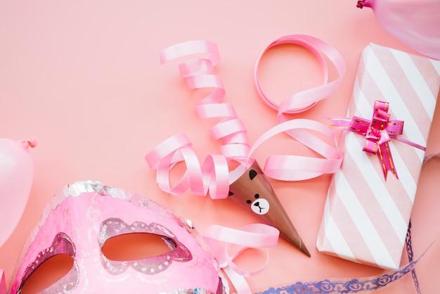 Máscara cerca de cinta y caja de regalo. Foto gratis