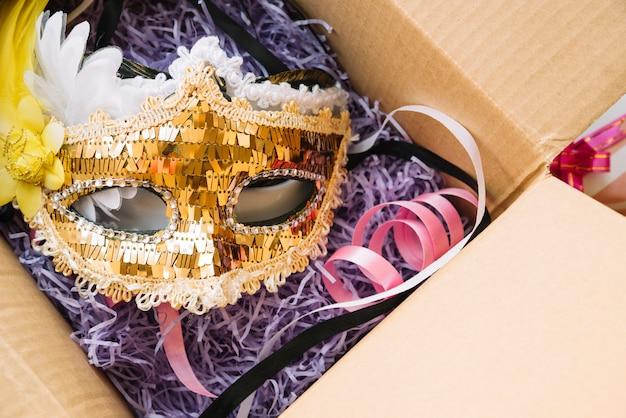 Máscara cerca de cinta colocada en caja artesanal Foto gratis