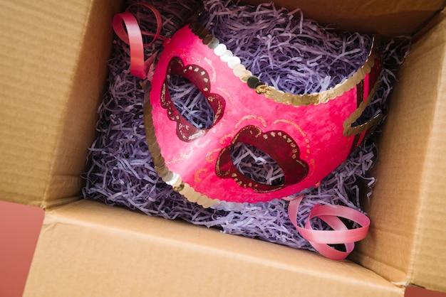 Máscara colocada en caja artesanal. Foto gratis
