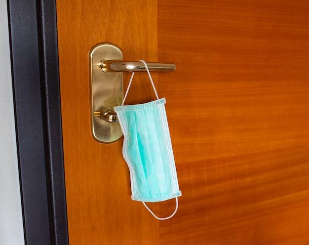 Máscara para evitar la infección del coronavirus covid 19, colgando de la manija de la puerta. concepto de prevención antes de salir de casa. Foto Premium