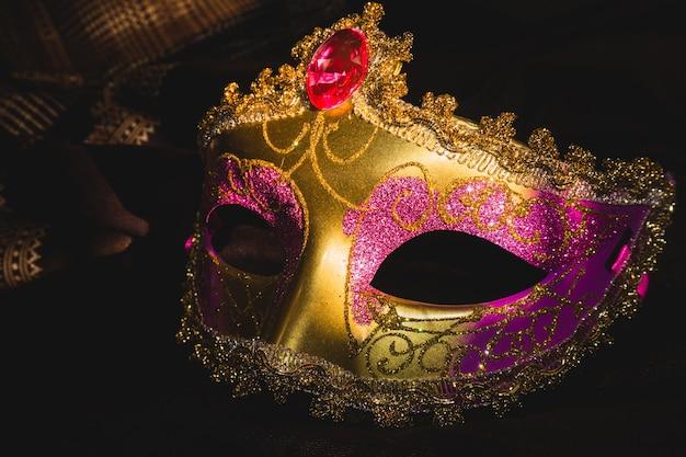 Máscara veneciana dorada y rosa sobre un fondo oscuro Foto gratis