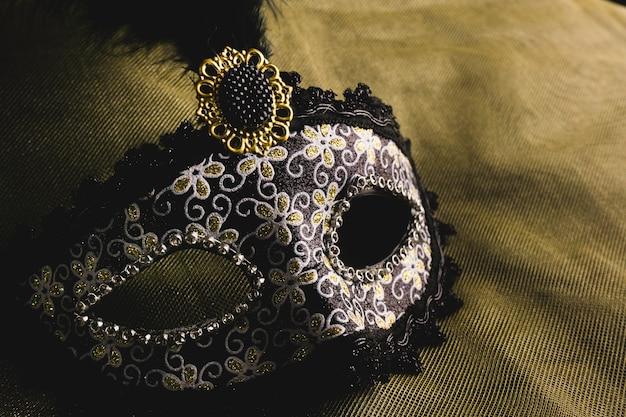 Máscara veneciana gris sobre un tela amarilla Foto gratis
