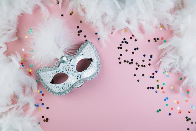 Mascarada de carnaval máscara de plumas con confeti colorido y boa de plumas sobre fondo rosa Foto gratis