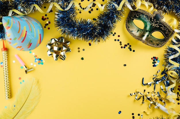 Mascarada de carnaval máscara de plumas con material de decoración de fiesta y sombrero de fiesta sobre fondo amarillo Foto gratis