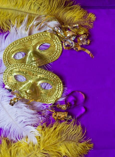 Máscaras y plumas de carnaval y superficie morada Foto Premium