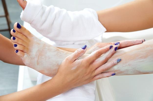 Mascarilla humectante nutritiva aplicando las piernas de la mujer. Foto Premium