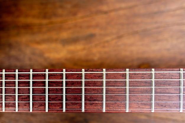 Mástil de una guitarra eléctrica sobre suelo de madera. Foto gratis