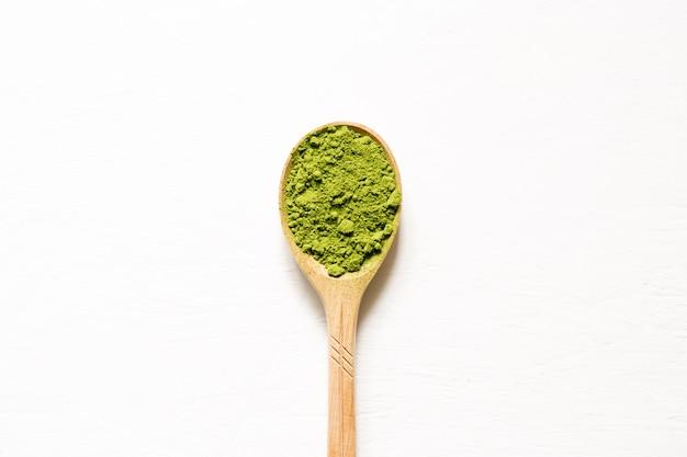 Matcha. té verde pulverizado japonés en una cuchara en un fondo blanco. vista superior y espacio de copia. Foto Premium