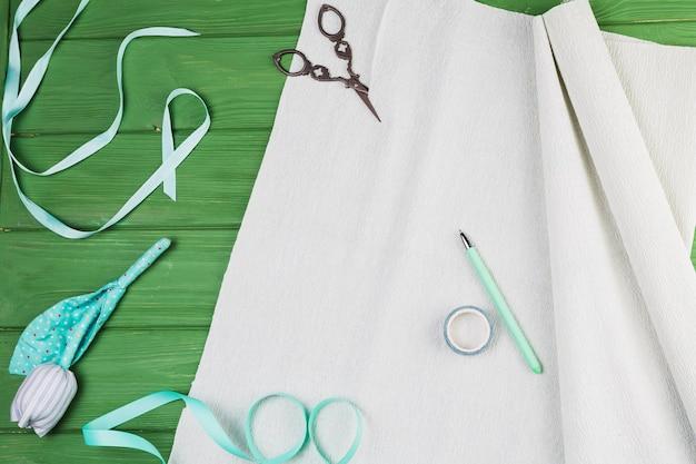 Material del arte de la mano con la flor falsa sobre fondo verde Foto gratis