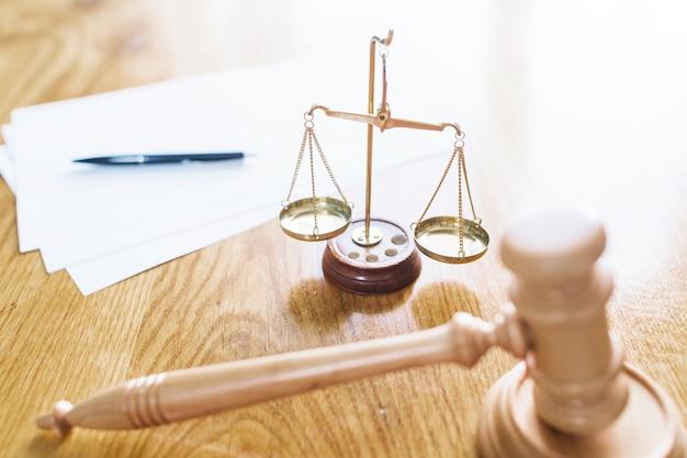 Mazo; escala de justicia; pluma y papeles en blanco en el escritorio de madera Foto gratis