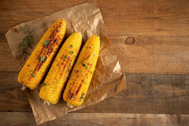 Mazorcas de maíz asadas a la parrilla en el fondo de madera. Foto gratis