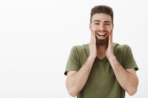 Me duelen las mejillas de reír y sonreír. retrato de hombre adulto barbudo atractivo optimista feliz divertido en camiseta verde oliva tocando la cara y sonriendo divirtiéndose estando de buen humor sobre la pared blanca Foto gratis