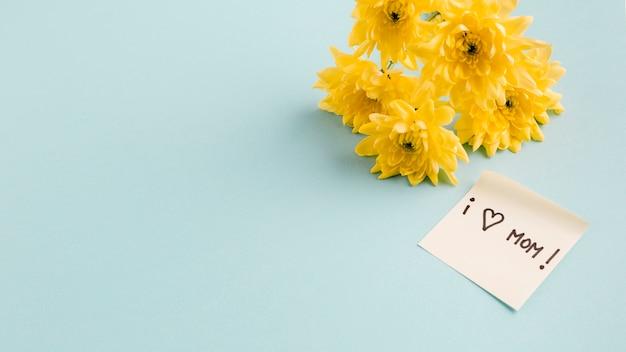 Me encanta el título de mamá en un papel cerca de un ramo de flores Foto gratis