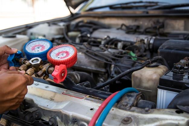 Mecánico de automóviles con herramienta de equipo de medición para el llenado de aire acondicionado de automóviles Foto Premium