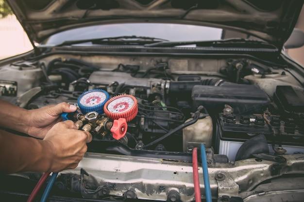 Mecánico de automóviles que utiliza la herramienta de equipo de medición para el llenado de los acondicionadores de aire de automóviles viejos. Foto Premium