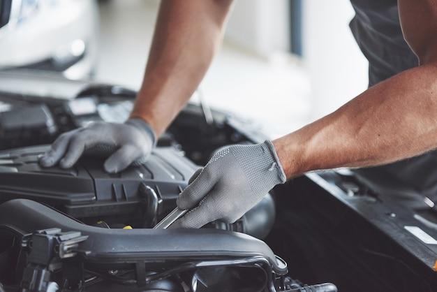 Mecánico de automóviles trabajando en garaje. servicio de reparación. Foto gratis