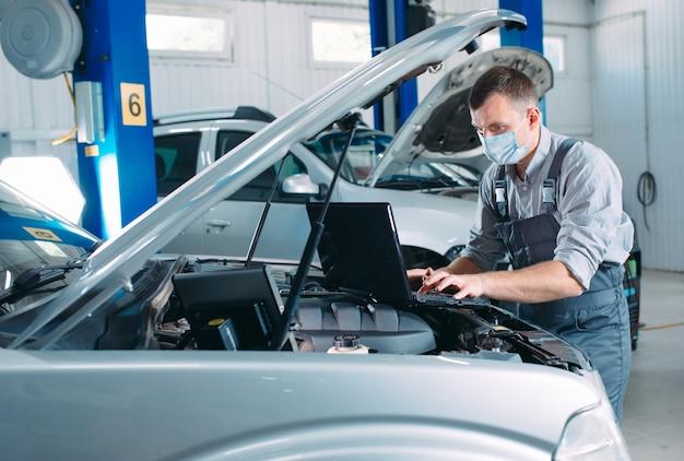 Un mecánico enmascarado revisa el automóvil en la estación de servicio. Foto Premium