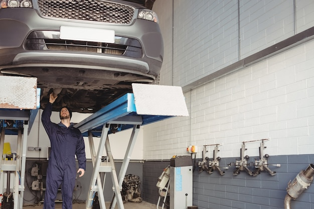 Mecánico examinando un coche Foto gratis