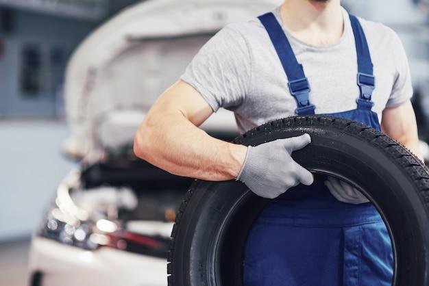 Mecánico sosteniendo un neumático en el garaje de reparación. reemplazo de neumáticos de invierno y verano Foto gratis